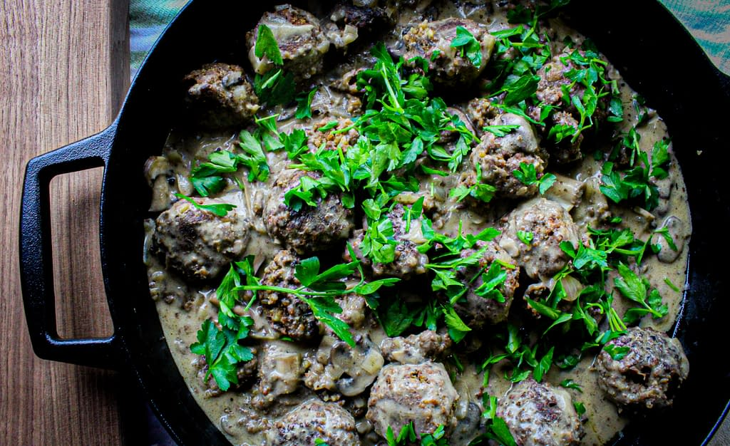 Meatballs and mushroom gravy with parsley on top.