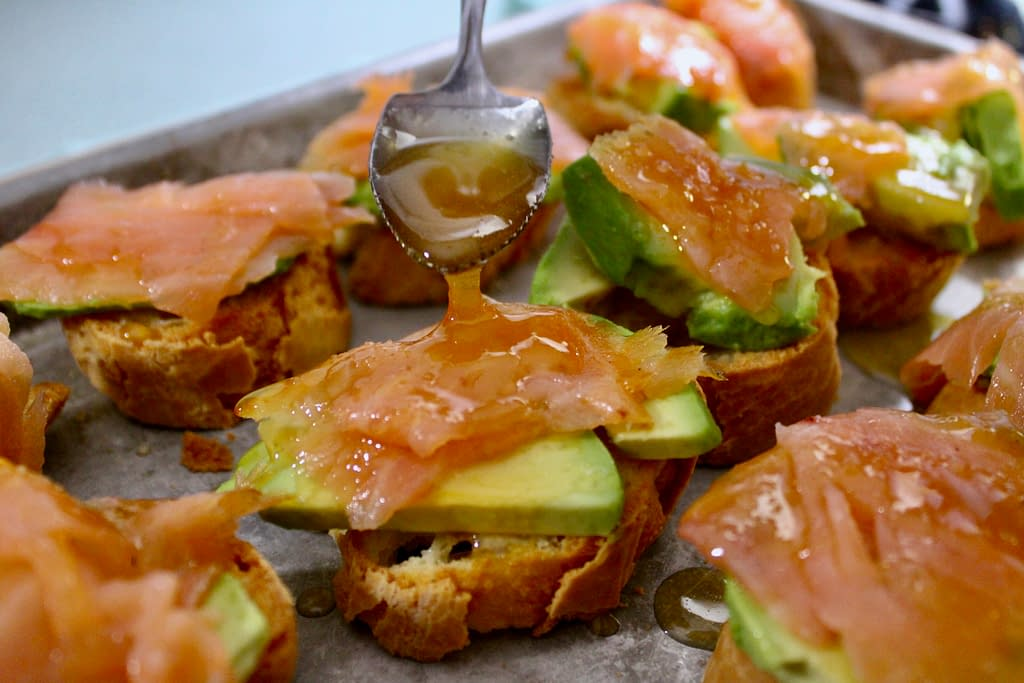 Drizzling honey over smoked salmon starters.