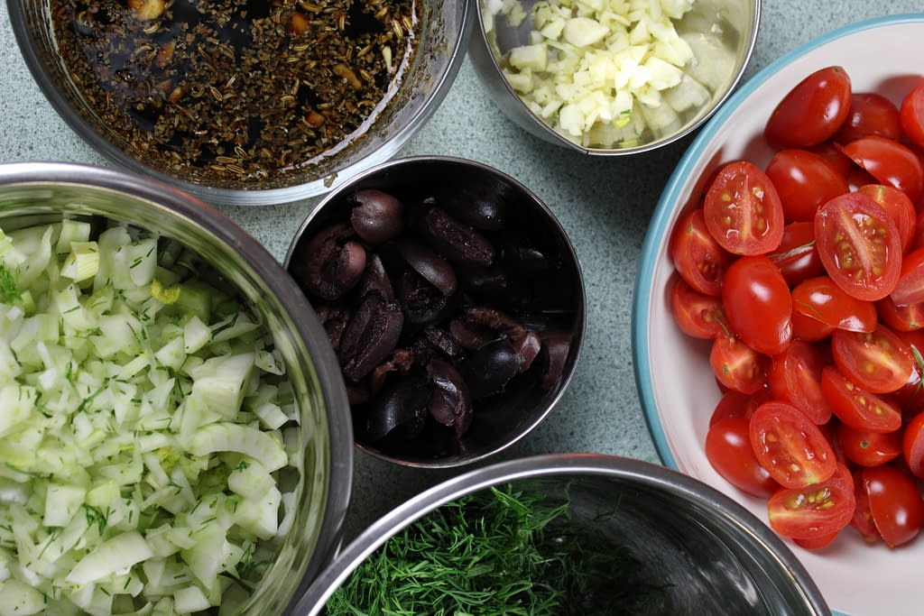 Ingredients like fennel, tomato, garlic, and olives for a tomato relish.
