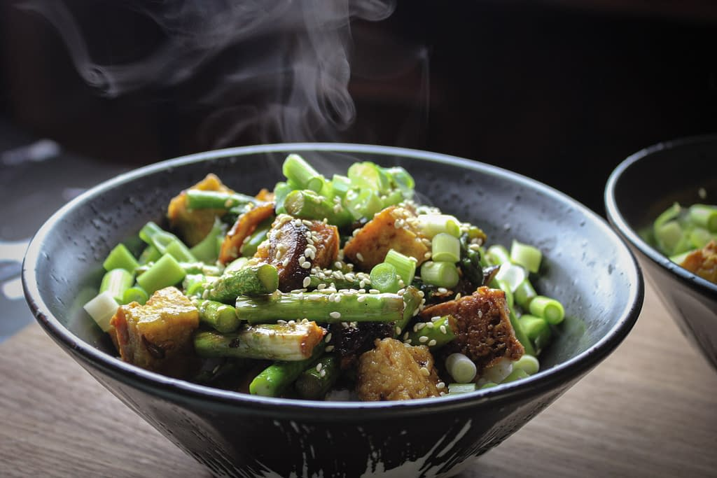 A steaming bowl of stir fry in a black bowl.