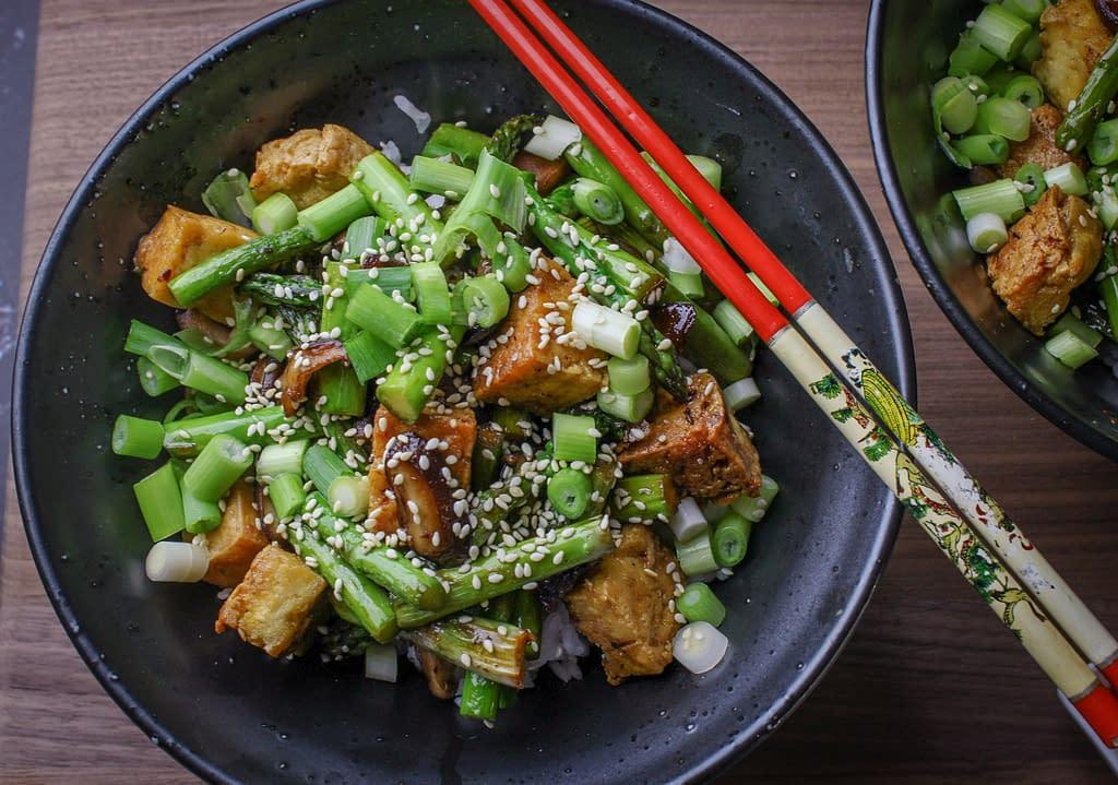 Tofu stir fry in a bowl with chopsticks
