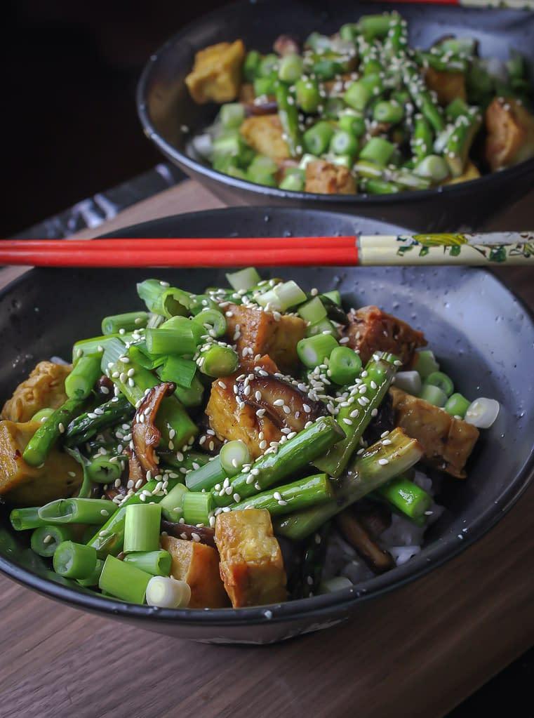 Tofu mushroom stir fry topped with scallions and sesame seeds.
