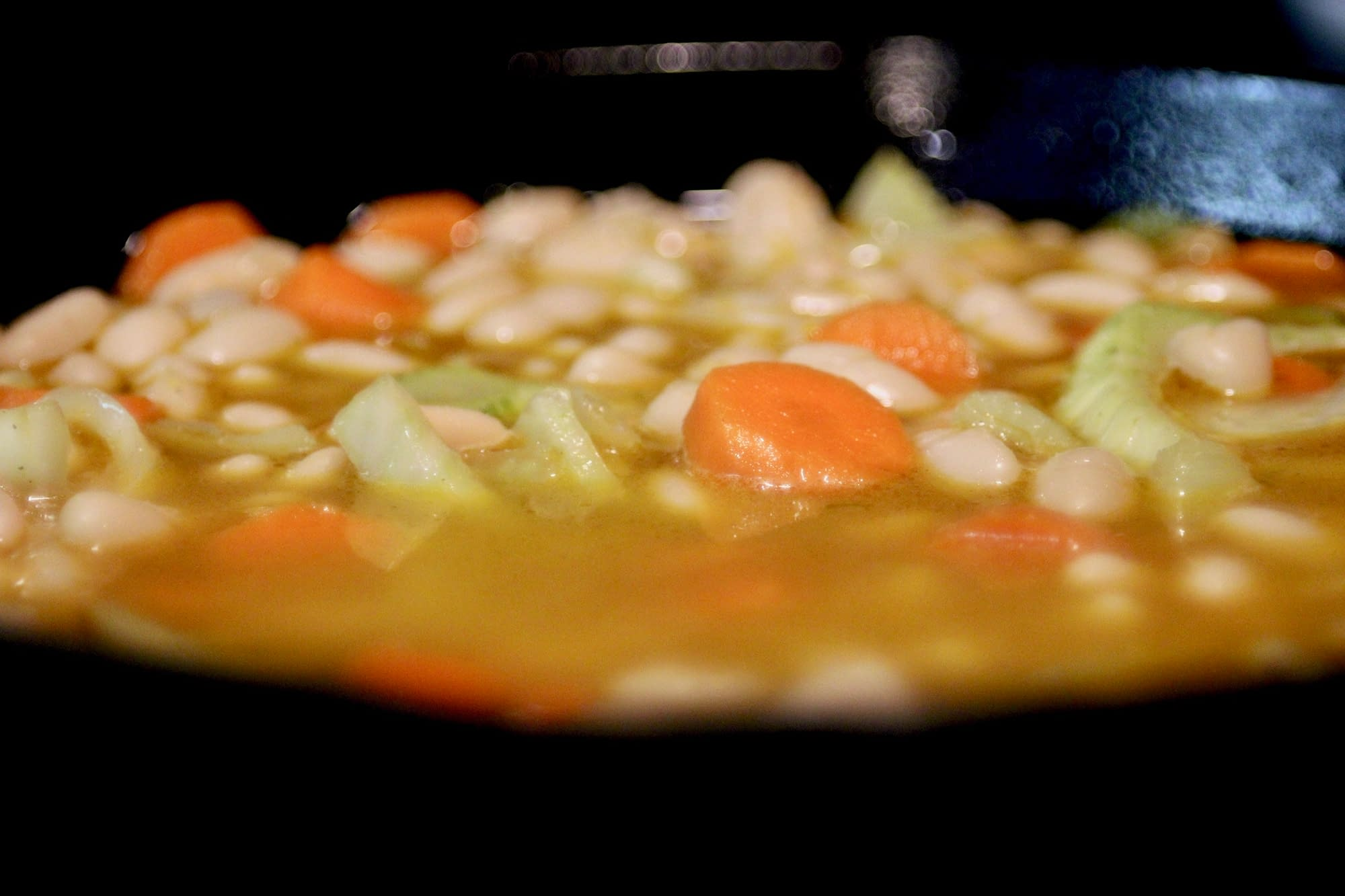 Adding the broth to the beans.