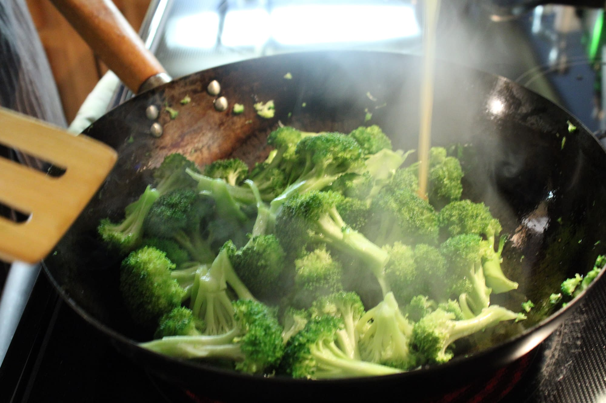 Cooking broccoli in a wok.
